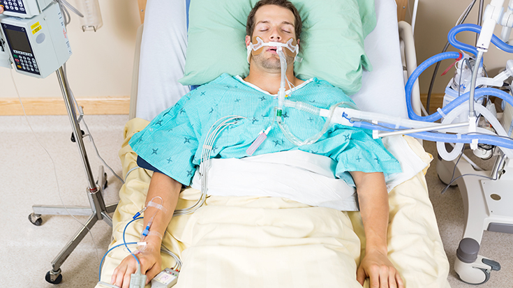 image of patient with breathing tube in hospital bed
