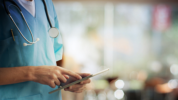 image of medical professional using electronic tablet