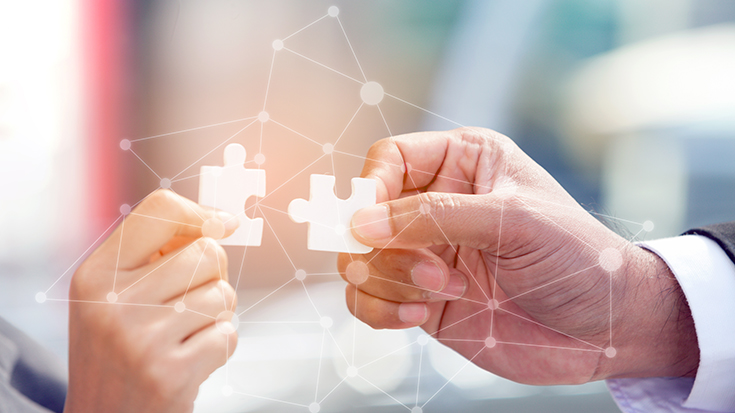 image of two people connecting two jigsaw puzzles