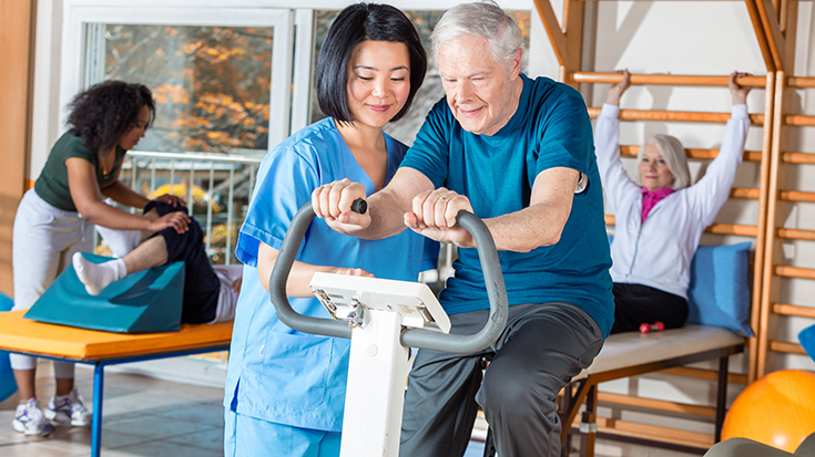 image of RT working with patient on exercise bike