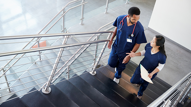 photo of two medical professionals walking up a staircase