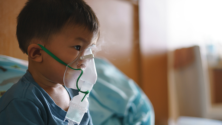 photo of young boy in hospital wearing nebulizer